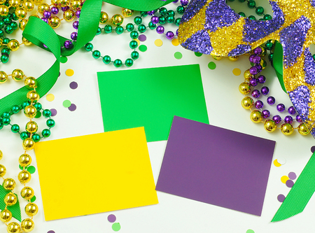 a beads: Green, gold and purple cards surrounded by matching beads, ribbons and confetti and a harlequin mask for a Mardi Gras image Stock Photo