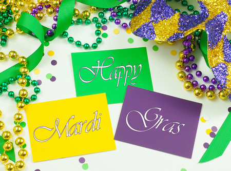 carnivale: Green, gold and purple cards surrounded by matching beads, ribbons and confetti and a harlequin mask for a Mardi Gras image Stock Photo