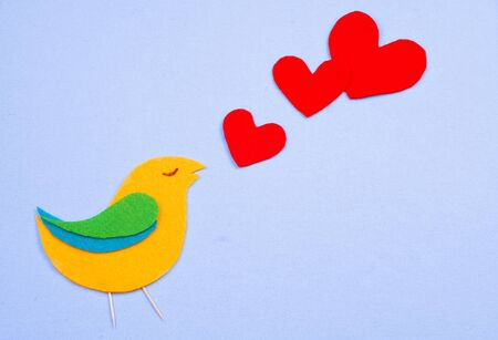 whimsy: A whimsical, felt cutout bird shape in yellow, green and blue with red felt hearts floating that represent the birds song. All are on a light blue cotton background. Copy space available. Stock Photo