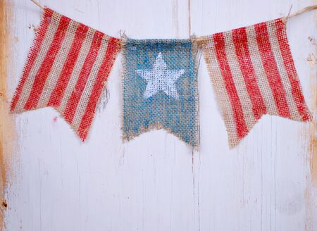 white washed: Rustic patriotic banner of three painted burlap flags on white washed wooden background. Center is white star on blue. Outside is red and white stripes for Flag day, July 4th and other USA holidays