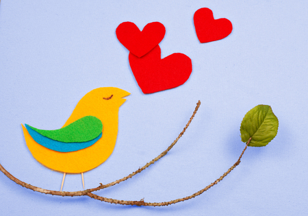 A whimsical, felt cutout bird shape in yellow, green and blue with red felt hearts floating that represent the birds song. The bird is sitting on a twig with a single green silk leaf. Stock Photo