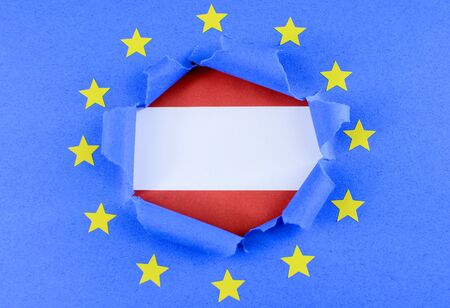 separatism: The red and white flag of Austria is shown behind the torn open center of the blue flag of the European Union with gold stars. Both flags are paper. The EU flag is highly textured construction paper.