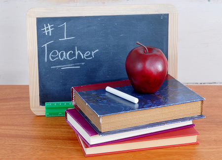 Number one teacher is written on a messy black chalkboard with old books in front. A red apple sits on top of the books with a piece of white chalk. Scene also includes a green ruler. Stock Photo