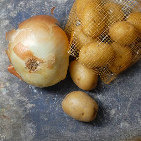 scarred: Flat lay, overhead perspective of a bag of Yukon Gold potatoes spilling out of a bag onto a scratched and stained steel surface. A vidalia onion lies next to them. Square image.