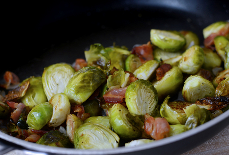 Closeup of roasted brussel sprouts with bacon and shallots in a frying pan. Green is the dominant color of this vegetable with red accents from the meat