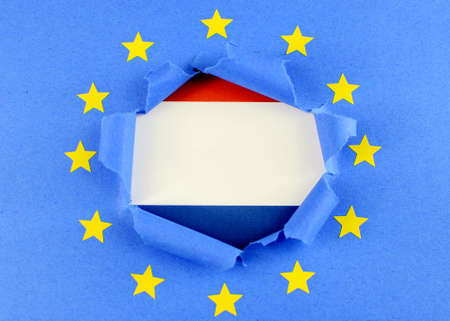 international crisis: The red, white and blue flag of the Netherlands is behind the torn open center of the blue flag of the European Union with gold stars. The EU flag is highly textured construction paper.