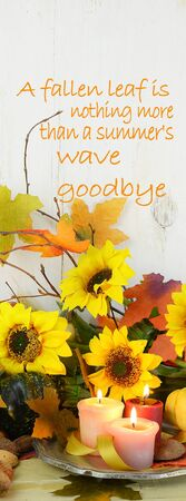 Fall still life with gourds, candles,  autumn leaves, twigs and sunflowers on a rustic wooden background with a vintage filter applied. Vertical banner sized with message added.