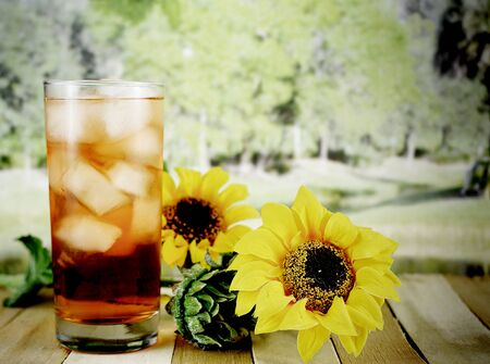 A glass of iced tea sitting on a wooden table with sunflowers with a blurred background of a tree lined lake in the sunshine. There are reflections on the glass from light and vintage filter applied Stock fotó