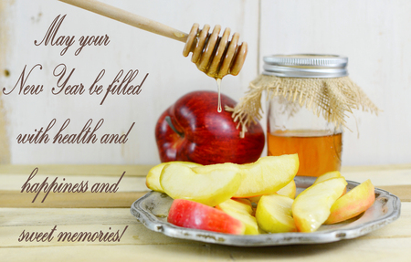 Rosh Hashanah image of honey and apple with sliced apple on a pewter plate. The honey is in a canning jar with burlap top and is being drizzled on the sliced apples from a honey dipper. Happy New Year greeting Stock Photo