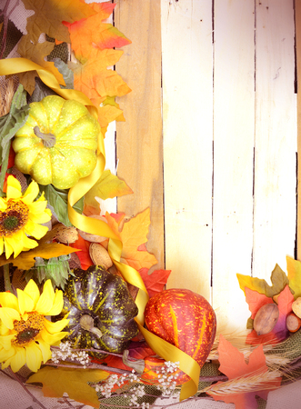 Thanksgiving or fall background with gourds, autumn leaves, twigs and sunflowers on a rustic wooden background with a vintage filter applied. Vertical orientation with copy space.