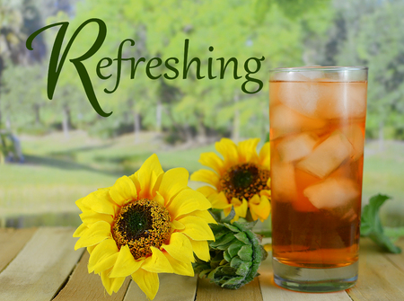 stating: A glass of iced tea sitting on a wooden table with sunflowers with a blurred background of a tree lined lake in the sunshine. Text stating  refreshing has been added Stock Photo