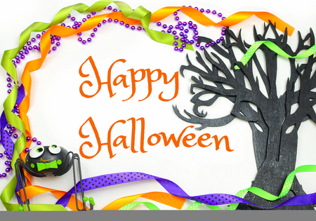 Halloween border of a rough textured wooden cutout of bare tree shape painted black. A silly spider and purple, green and orange ribbons and beads frame the Happy Halloween message Stock Photo