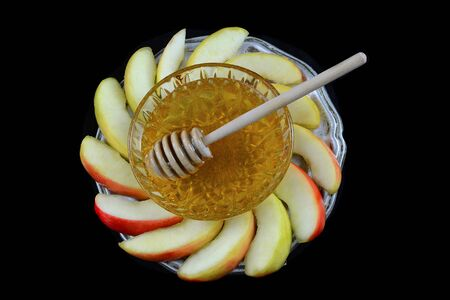 Rosh Hashanah low key image of honey and apple on a pewter plate. The honey is in a crystal bowl. All on a black background.