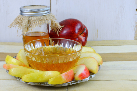 Rosh Hashanah image of honey and apple with sliced apple on a pewter plate. The honey is in a canning jar with burlap top. Copy space