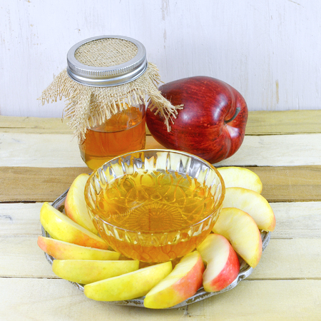 Rosh Hashanah image of honey and apple with sliced apple on a pewter plate. The honey is in a canning jar with burlap top. Square aspect ratio