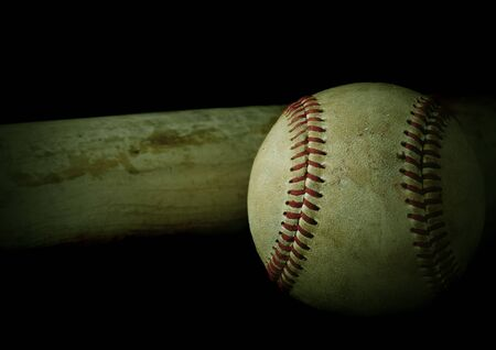 Low key image of old baseball and bat showing pine tar residue on black background. Vintage filter applied