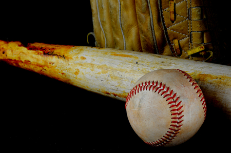 Low key image of old baseball and bat showing pine tar residue on black background. A baseball mitt is in the background. Shallow depth of field