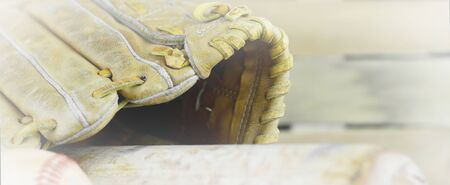 mitt: Banner shaped image of old leather baseball mitt, or glove, and bat on wooden background. White vignette added.