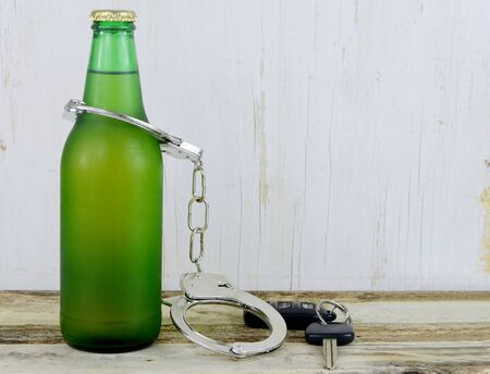 dwi: A single beer in a green bottle on a wooden table with rustic wooden background. Handcuffs and keys to symbolize dangers of drinking and driving
