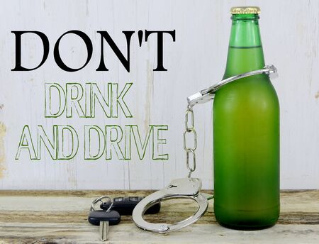 dwi: A single beer in a green bottle on a wooden table with rustic wooden background. Handcuffs and keys and text message added.