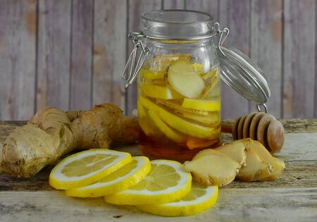 Closeup image of ingredients for natural cold or flu remedy includes ginger, honey in a jar, a honey drizzler and lemon on a wooden background. Stock Photo