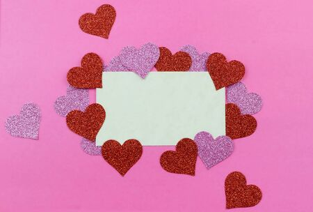Sparkly pink and red hearts surround a parchment paper tage on a bright pink background for Valentines Day in February. Copy space.