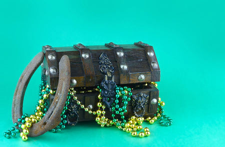 Image for Saint Patricks Day on March 17th. Treasure chest to symbolize luck and wealth filled with shiny green and gold beads. A lucky horseshoe is shown. Copy space Stock Photo