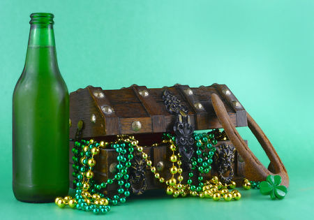 Image for Saint Patricks Day on March 17th. Treasure chest to symbolize luck and wealth. A bottle of beer and a lucky horseshoe are added. Copy space.