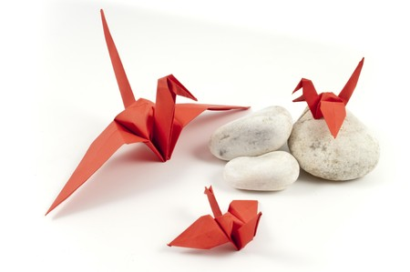 Red Origami Crane and his childres on white stones Stock Photo