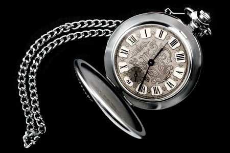 Old pocket watch with chain isolated on black background photo