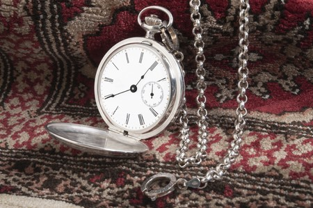 watch over: Elegant silver pocket watch over a carpet