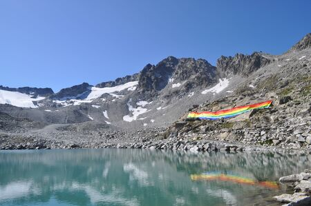 peace flag: Peace flag dropped in mountain reflected in a lake, Adamello Italy