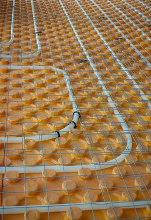 Orange posed Underfloor heating tube in a construction site photo