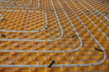tubing: Orange posed Underfloor heating tube in a construction site