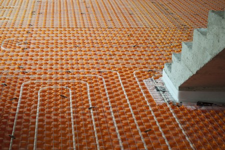 Orange Underfloor heating tube in a construction site with stairs