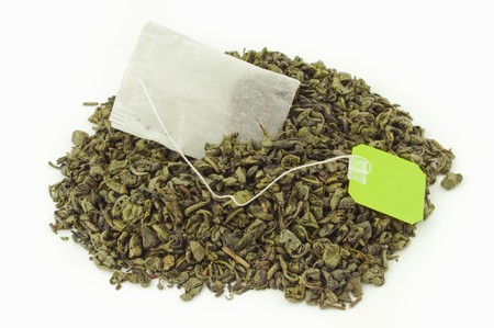 Tea bag inside a mount of dried green tea leaves Stock Photo