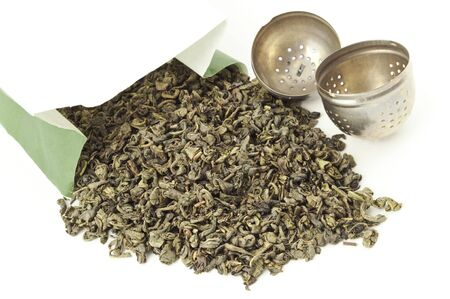 tea filter: Little bag of dried green tea leaves isolated on white with tea metal filter
