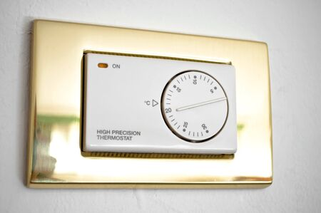 High precision thermostat on a white wall photo