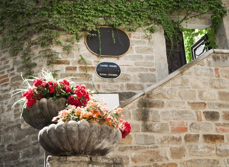 Exterior hotel and resturan sign in a stone wall with flower  Stock Photo