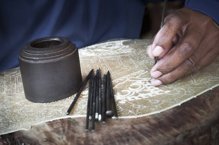 Traditional craftsman carving wood making indonesian puppets