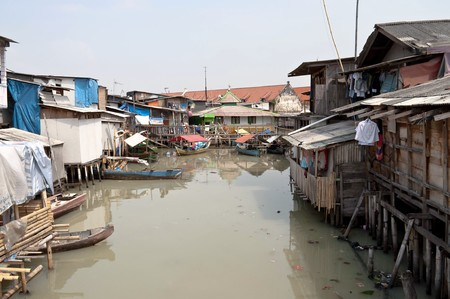 slum: Slum on dirty canal in Jakarta, Indonesia Stock Photo