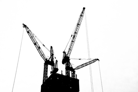 cranes: Black and white silhouette crane on top an under construction  building  Stock Photo