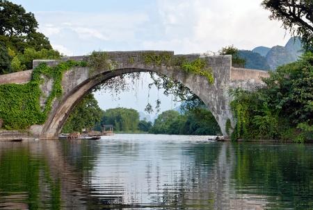 Chinese stone bridge landscape on li river with bridge reflection on water photo