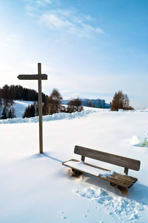 Wooden Winter bench with mark trial in winter snow scape photo