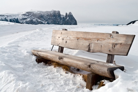 Isolated wooden bench on snow scape in dolomiti, Alps photo