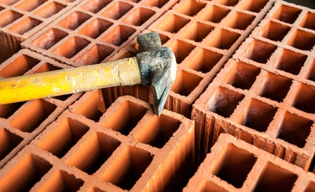 Hollow brick with an hammer on construction site photo