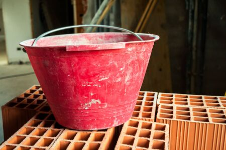 Masonry bucket on hollow bricks in construction site photo