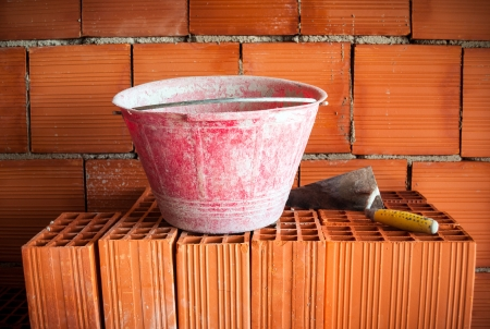 Trowel and bucket on a brick wall in a mansory workplace photo