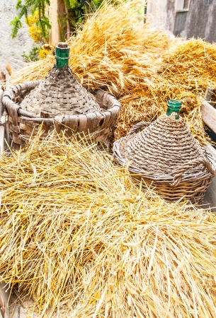carboy: Autumn harvest demijohn wicker with bales of hay Stock Photo