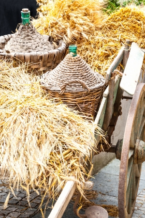 demijohn: Autumn wooden cart harvest and demijohn wicker with bales of hay